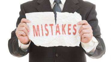 Businessman tearing paper which written mistakes word